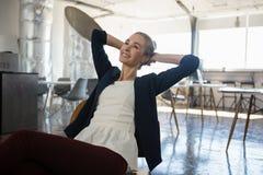 Femme d'affaires réfléchie avec des mains derrière la tête détendant sur la chaise photographie stock libre de droits