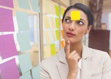 Femme d'affaires réfléchie avec la note collante vide sur le front photographie stock libre de droits