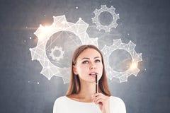 Femme d'affaires réfléchie, roues dentées, mur gris illustration libre de droits