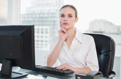 Femme d'affaires réfléchie s'asseyant au bureau regardant l'appareil-photo Photographie stock libre de droits