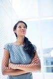 Femme d'affaires réfléchie se tenant dans le bureau Images stock