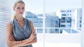 Femme d'affaires réfléchie se tenant dans le bureau Image libre de droits