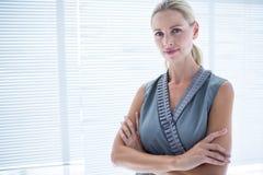 Femme d'affaires réfléchie se tenant dans le bureau Images libres de droits
