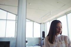 Femme d'affaires réfléchie se tenant dans le bureau Photographie stock libre de droits