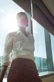 Femme d'affaires réfléchie se tenant prêt la fenêtre brillamment allumée dans le bureau Photo libre de droits