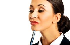 Femme d'affaires réfléchie tenant un stylo photographie stock