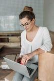 Femme d'affaires réfléchie travaillant avec l'ordinateur portable tout en se reposant sur les cubes en bois Photos stock