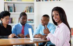 Femme d'affaires réussie d'afro-américain avec l'équipe et l'ordinateur photographie stock