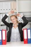 Femme d'affaires réussie With Arms Raised dans le bureau Image libre de droits