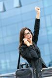Femme d'affaires réussie au téléphone soulevant le bras Photo libre de droits