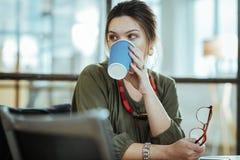 femme d'affaires réussie aux cheveux foncés ayant la pause-café dans le bureau photographie stock libre de droits