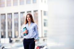 Femme d'affaires réussie avec le bloc-notes tout en marchante extérieure Fonctionnement de femme d'affaires de ville Images libres de droits