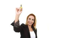 Femme d'affaires réussie blonde attirante tenant l'écriture de marqueur sur le conseil transparent Photo stock