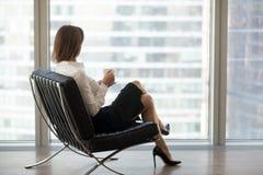 Femme d'affaires réussie s'asseyant dans la chaise confortable appréciant v images stock