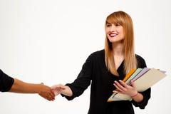 Femme d'affaires réussie tenant la poignée de main de dossiers saluant au-dessus du fond blanc Images stock