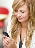Femme d'affaires radiante envoyant un message avec texte Images stock