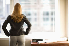 Femme d'affaires regardant à l'extérieur l'hublot Images stock