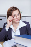 Femme d'affaires regardant au-dessus du RIM de ses glaces Images libres de droits