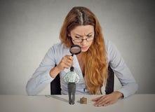 Femme d'affaires regardant avec scepticisme le petit employé par la loupe Photos libres de droits