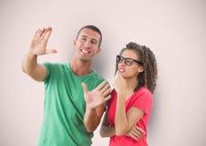 Femme d'affaires regardant le collègue faisant des gestes au-dessus du fond coloré Photographie stock