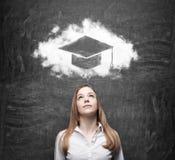 Femme d'affaires regardant le nuage avec le chapeau d'obtention du diplôme au-dessus de la tête Image libre de droits