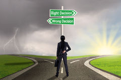 Femme d'affaires regardant le signe de la droite contre la décision fausse Image libre de droits