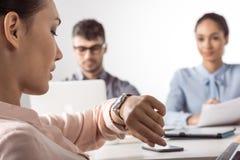 Femme d'affaires regardant les montres actuelles tandis que ses collègues travaillant le bureau Photographie stock libre de droits