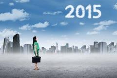 Femme d'affaires regardant les numéros 2015 sur le ciel Image libre de droits