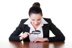Femme d'affaires regardant par la loupe sur la table. Images libres de droits