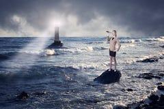 Femme d'affaires regardant par un télescope contre la mer orageuse avec le phare photos stock