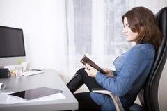 Femme d'affaires Relaxing sur sa chaise lisant un livre image stock