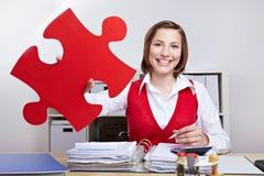 Femme d'affaires retenant la partie rouge de puzzle denteux Photo stock