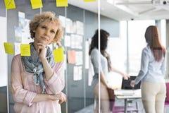 Femme d'affaires réfléchie lisant les notes collantes sur le verre avec des collègues à l'arrière-plan Image stock