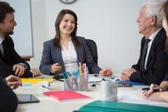 Femme d'affaires riant au cours de la réunion d'affaires Photographie stock libre de droits
