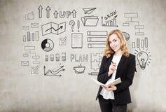 Femme d'affaires rousse avec un carnet près d'un mur en béton avec photos libres de droits