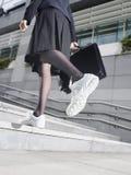 Femme d'affaires In Running Shoes marchant vers le haut des étapes image libre de droits