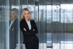 Femme d'affaires sérieuse avec les bras pliés dans le bureau Images stock
