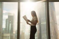 Femme d'affaires sérieuse occupée tenant le document de lecture, Ne debout Photographie stock