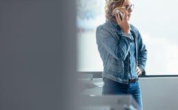 Femme d'affaires sérieuse parlant sur le téléphone portable Images stock