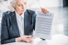 Femme d'affaires sérieuse s'asseyant sur le lieu de travail et se dirigeant au contrat Photo stock