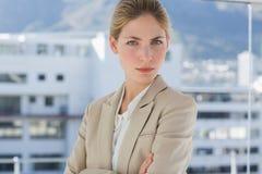 Femme d'affaires sérieuse se tenant dans le lieu de travail image stock