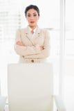 Femme d'affaires sérieuse se tenant derrière sa chaise Photographie stock