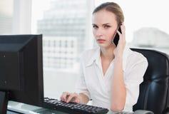 Femme d'affaires sérieuse sur le smartphone regardant l'appareil-photo Photos stock