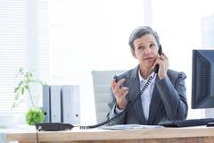 Femme d'affaires sérieuse téléphonant et à l'aide de l'ordinateur Image libre de droits