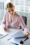 Femme d'affaires sérieuse travaillant avec des documents Photographie stock