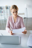Femme d'affaires sérieuse travaillant avec des documents Photographie stock libre de droits