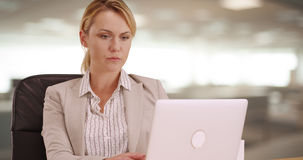 Femme d'affaires sérieuse travaillant sur l'ordinateur portable Photographie stock libre de droits
