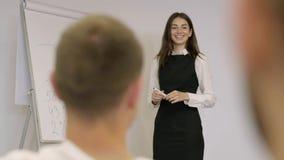 Femme d'affaires sûre mignonne présent le nouveau projet aux associés avec le tableau de conférence Meneur d'équipe présentant l' banque de vidéos