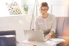 Femme d'affaires sûre sérieuse travaillant sur l'ordinateur portable Photographie stock libre de droits