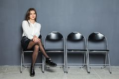 Femme d'affaires sûre s'asseyant sur la chaise et l'entrevue de attente sur le fond gris Photos stock
